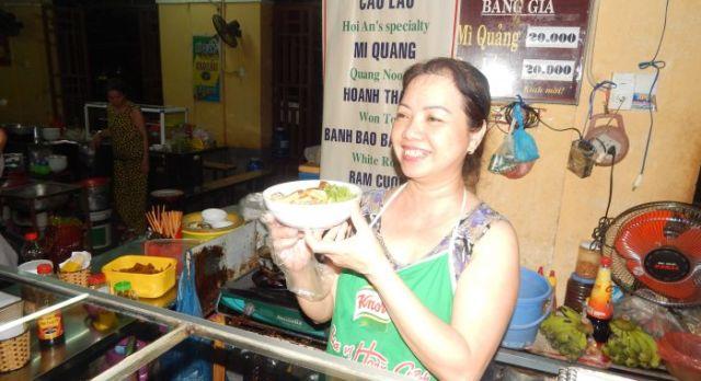 An einem Streetfood Stand serviert eine Marktfrau vietnamesisches Essen