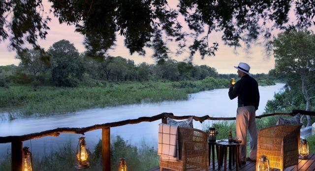 Mann steht und trinkt auf einer Außenterrasse am Ufer