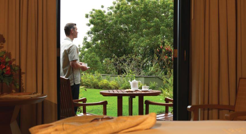 Mann steht im Garten und trinkt Tee