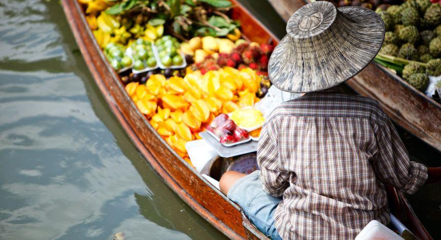Frau auf einem Boot auf einem schwimmenden Markt in Thailand