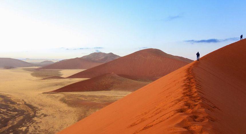 Zwei Menschen gehen eine Sanddüne der Namib-Wüste in Namibia entlang