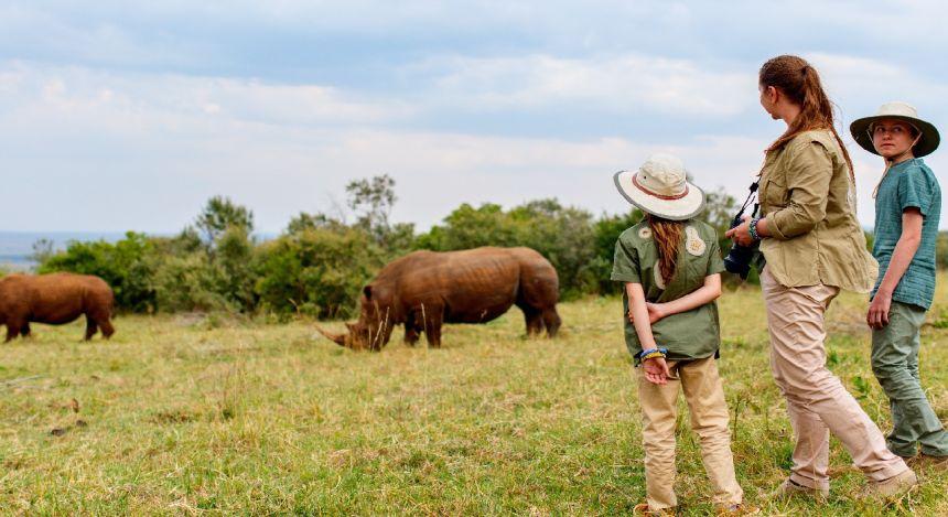 Kind betrachtet grasendes Nashorn