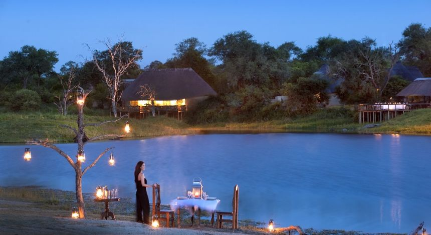 Woman standing at outside dining table of Arathusa Safari Lodge