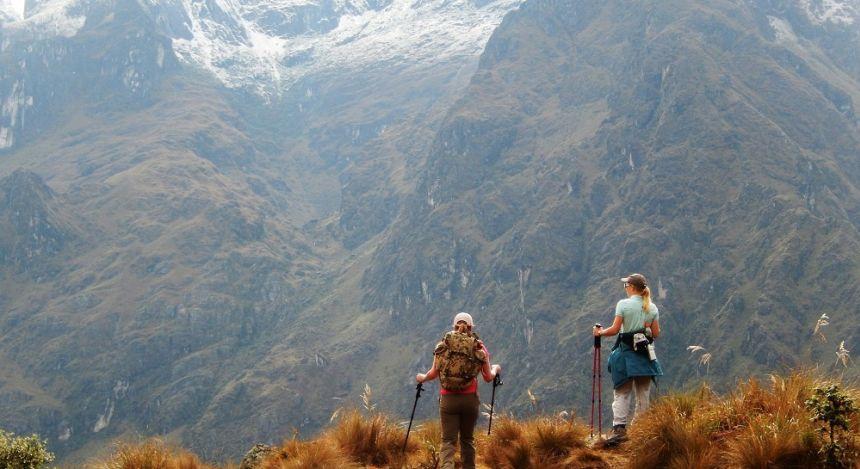 Zwei Wanderer blicken auf Bergkulisse