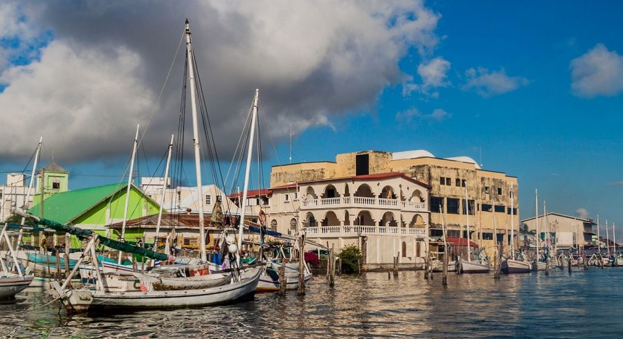 Enchanting Travels Belize Tour Houses and yachts at a sea coast in Belize City.