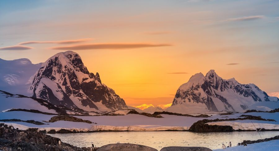 Enchanting Travels Antarctica Tours Beautiful snow-capped mountains against the sunset sky in Antarctica