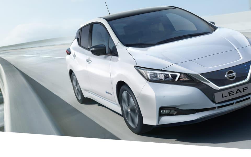 Hvit Nissan Leaf kjører mot kamera over bro
