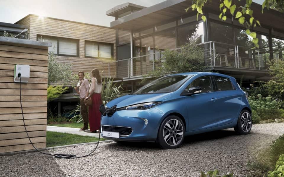 Par på vei inn i huset mens blå Renault Zoe lader i hagen foran moderne hus