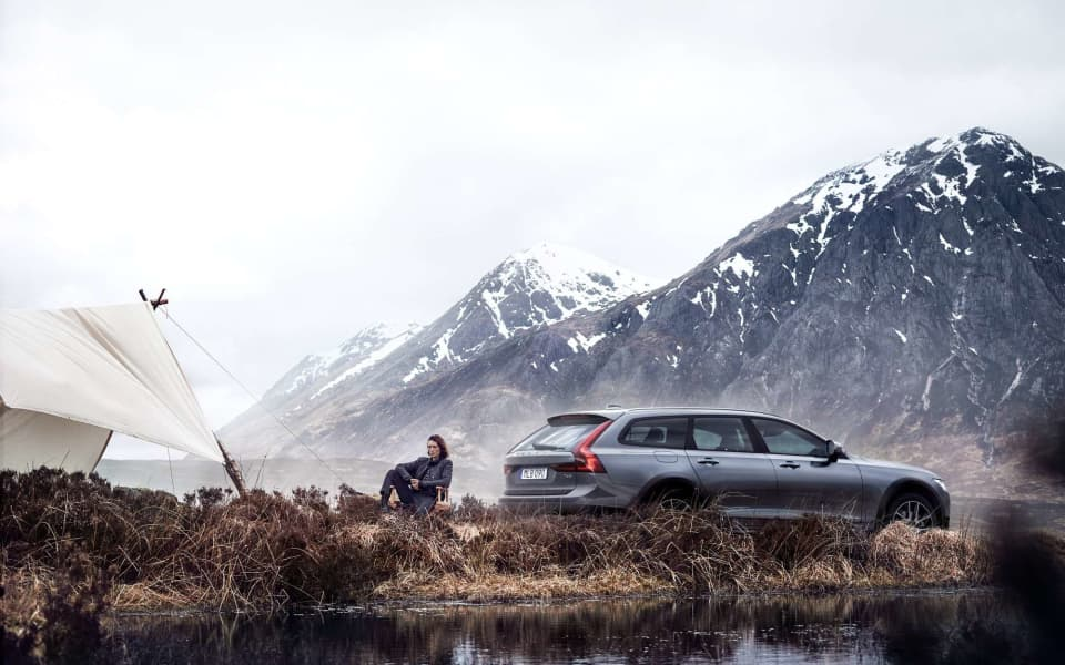 Volvo V90 Cross Country parkert i nordisk natur foran et telt med en dame