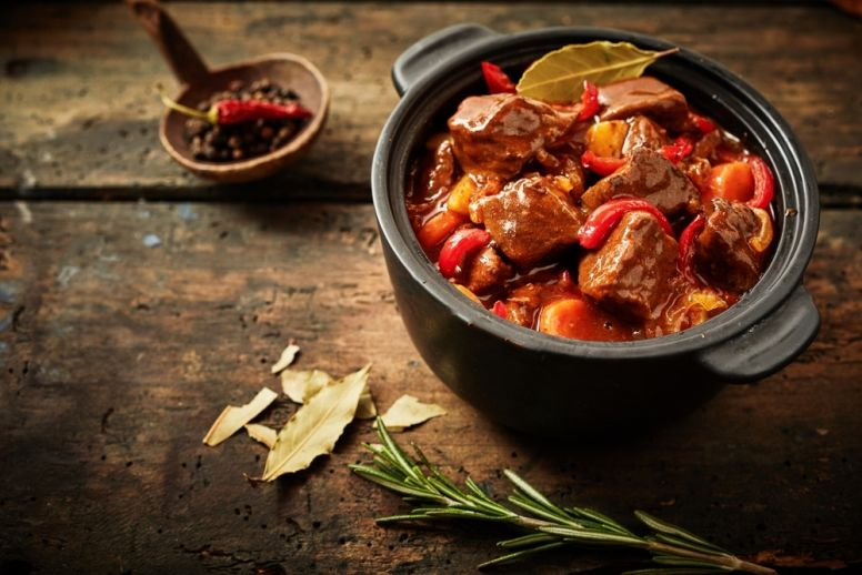 A Pot of Hungarian Goulash Stew with a Sprig of Rosemary on the Side