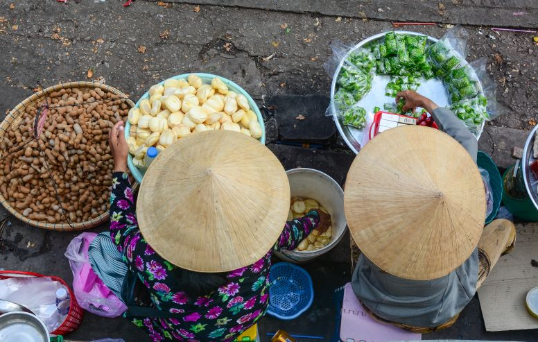 women with conical hats serving bowls of food