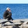 Old man sitting on the breakwater - acciaroli.info