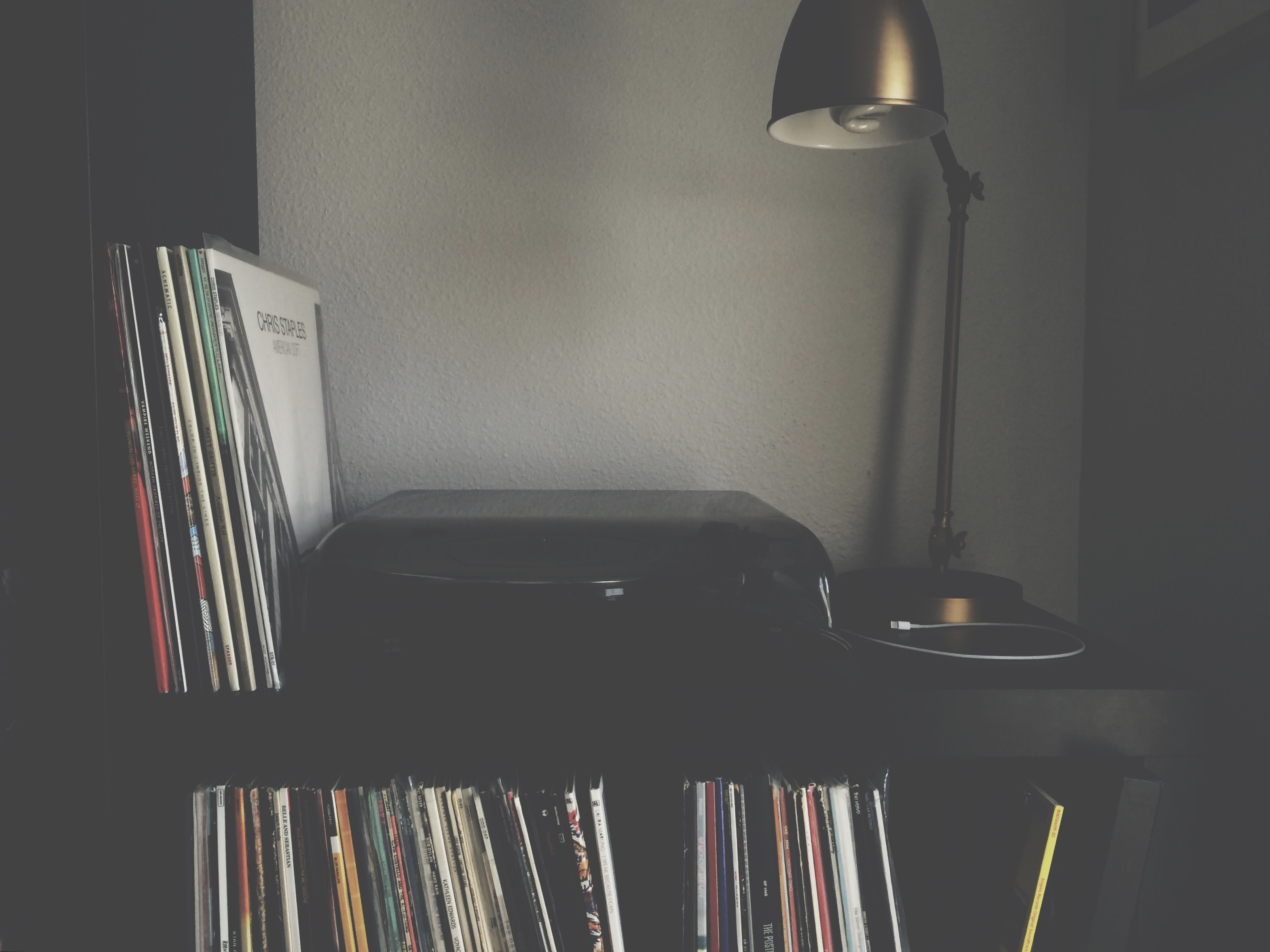 A turntable sitting on shelves filled with records.