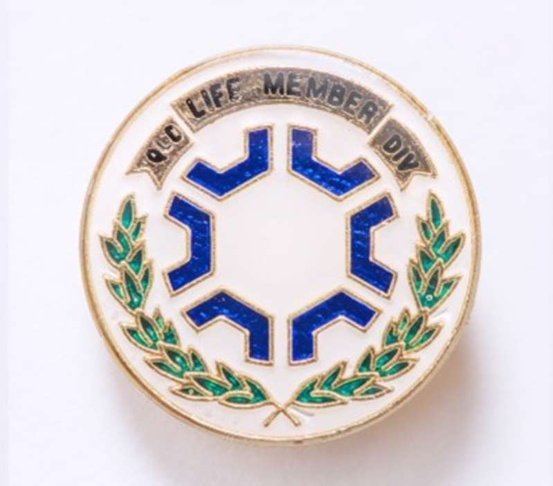 A white, blue and green circular  badge with gold edges and text that reads Life Member.