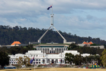 The Australian national flag flies above Parliament House. The flag atop the massive steel flagpole is the size of a double decker bus. The flag at Old Parliament House is much smaller but no less symbolic. Image: Museum of Australian Democracy Collection. Photographer: Andrew Merry.