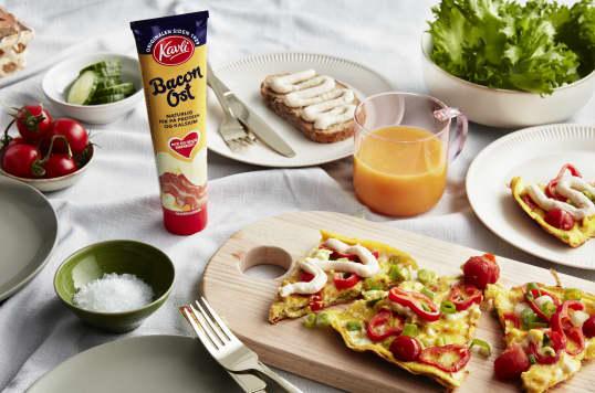 Kavli Baconost er en deilig smaksetter i frokostomeletten. Her ser du en fargerik omelett med paprika, vårløk, tomat og baconost.