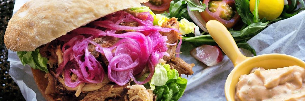 Pulled pork som får en härlig smak av liquid smoke, kalvfond, rödvin och kryddor. Servera i hamburgerbröd tillsammans med chili bearnaise, aioli, picklad rödlök och en god sallad.