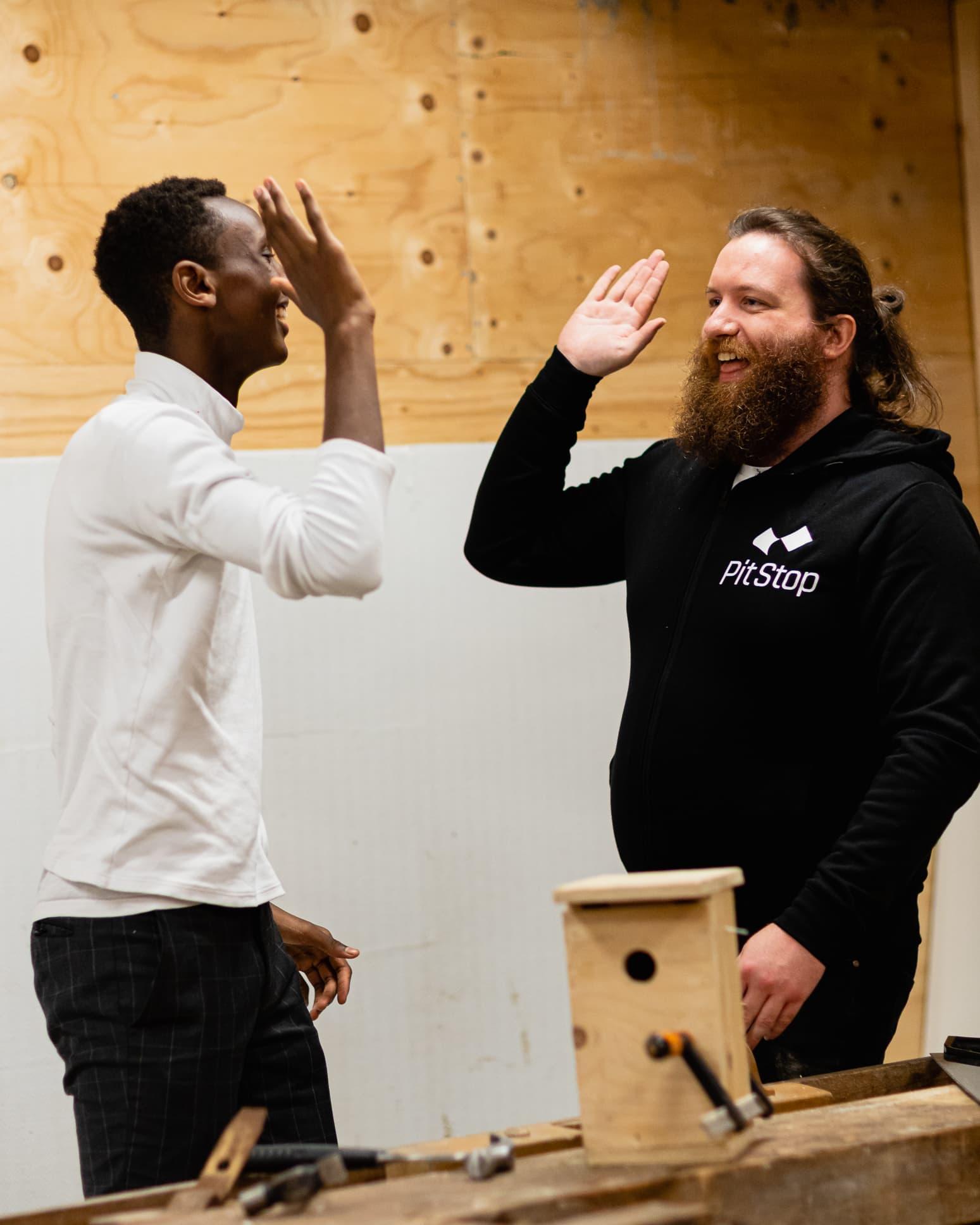 High five mellom en ungdom og en PitStop-medarbeider! Hos PitStop får ungdommen tildelt en rekke mestringsverktøy som skal gjøre dem mer robust i møte med livet generelt og skole og arbeid spesielt.