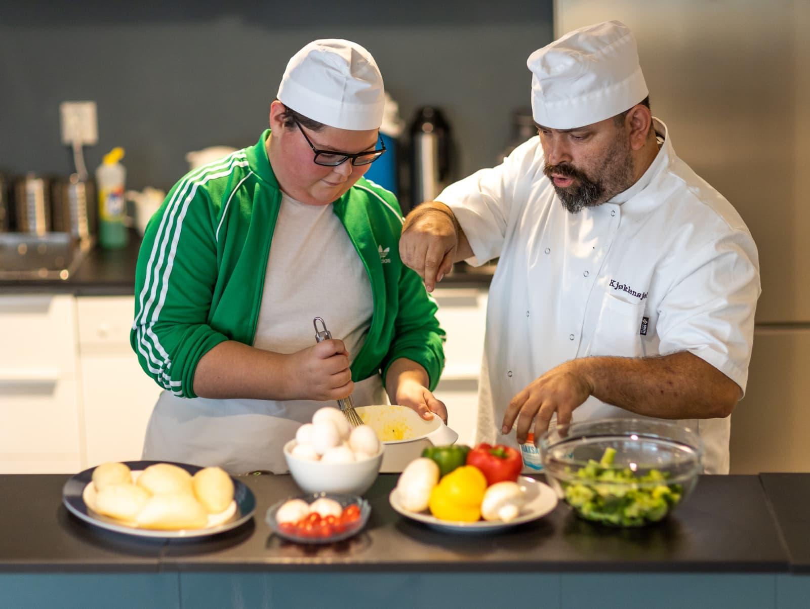 En PitStop-ungdom lager mat med en kjøkkensjef. Rundt 80 % av ungdommen som deltok i PitStops pilotprosjekt mellom 2016 og 2019kom seg tilbake i skole, arbeid eller annen tilrettelagt aktivitet.