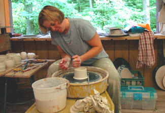 An artists uses a potter's wheeland clay at the Touchstone Center for Crafts