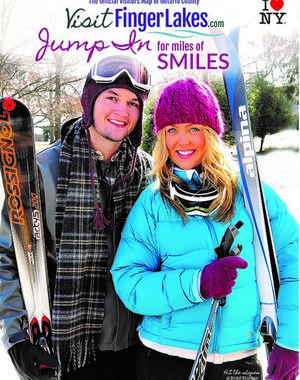 "A young couple stands with skiing equipment, smiles on their faces. The title of the guide read ""Visitfingerlakes.com, Jump in for miles of smiles."""