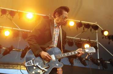 Alejandro Escovedo with shades and a guitar, live and in concert with lights on stage.
