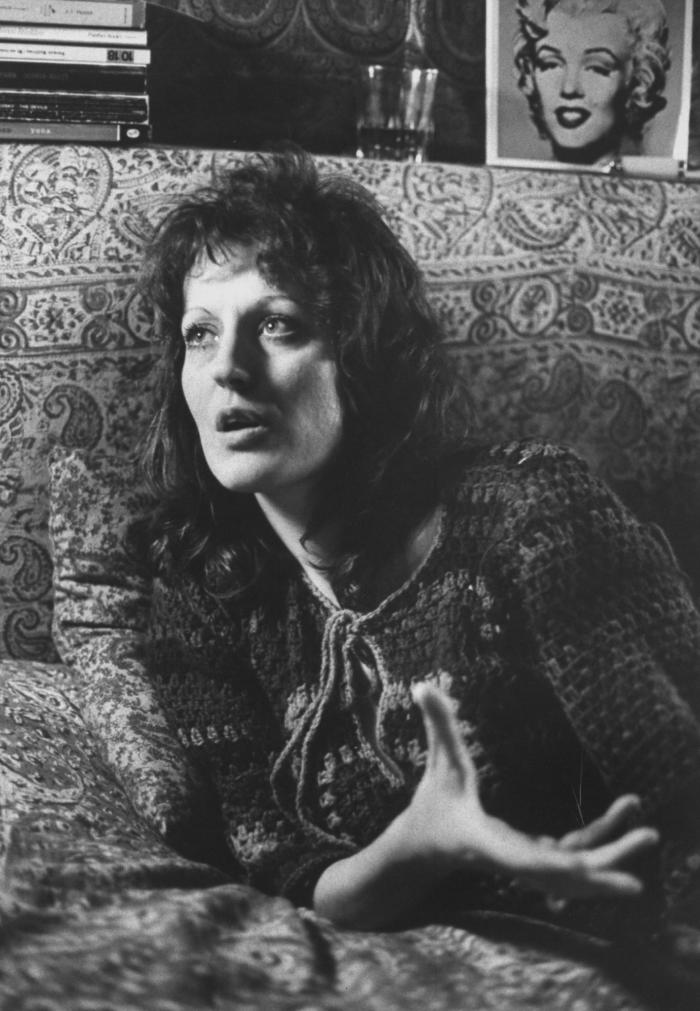 """Germaine Greer and paisley sofa. A cropped version of this photograph, minus the print of Warhol's Marilyn Monroe, was published in LIFE with the tagline """"The feminist who is against sexism but not sex"""". Picture: Terence Spencer/The LIFE Picture Collection/Getty Images."""