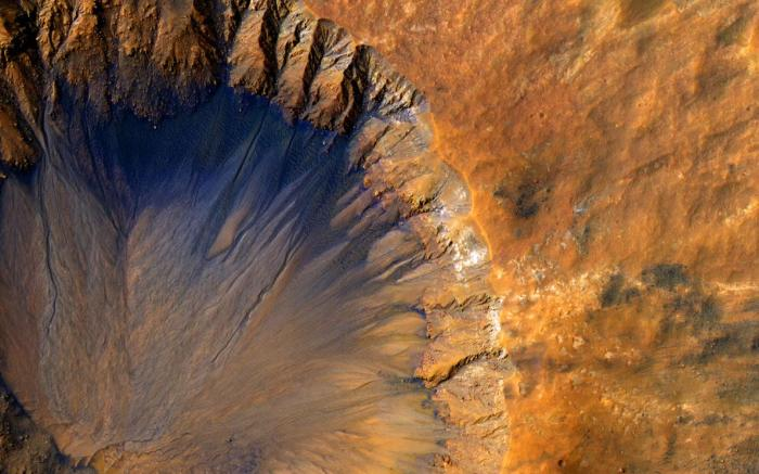 Traces of salty water have been detected in gullies and craters on Mars, such as this impact crater with dark streaks along its inner edge. Picture: NASA